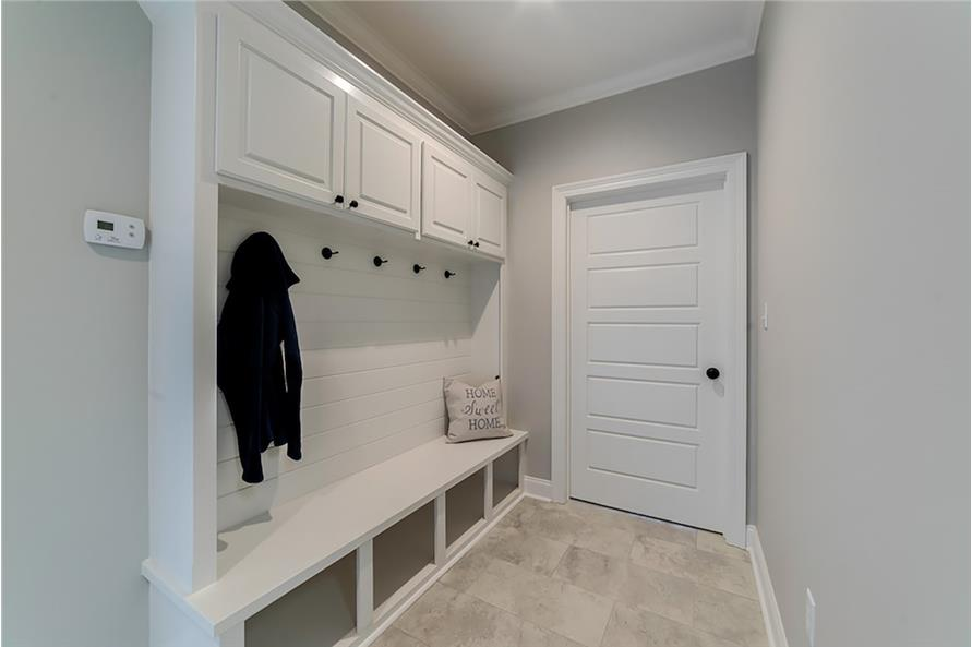 Mudroom with white overhead cabinets, coat racks, and built-in storage that doubles as a bench.