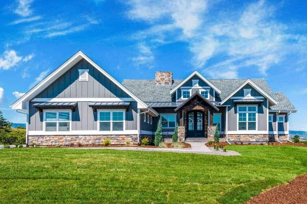 This is the front of the house adorned with multiple windows and gray shiplap exterior walls with stone mosaic base accents that go well with the shrubs planted on the sides of the concrete walkway and grass lawn.