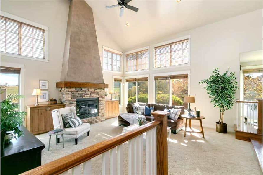 Living room with cozy seats, a stone fireplace, and plenty of windows that bring ample natural light in.