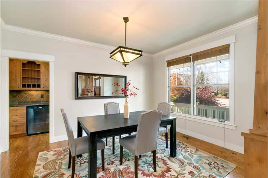 Formal dining room with a floral area rug. four-seater dining set, and a rectangular mirror adorning the beige walls.