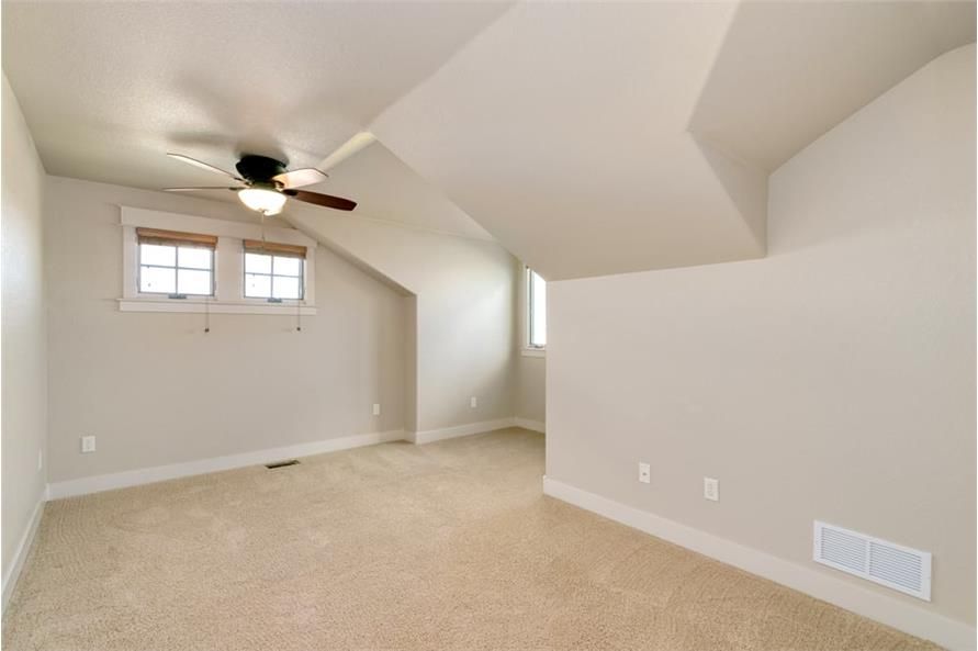 Bedroom with vaulted ceiling, beige walls, and small windows that invite natural light in.