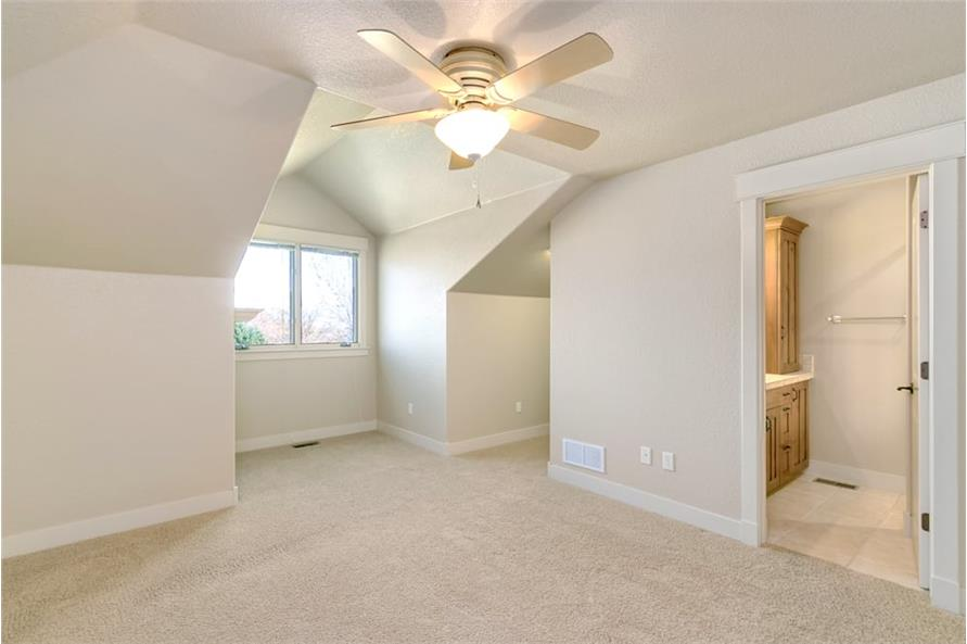 Another bedroom with carpet flooring, vaulted ceiling, and a private bath.