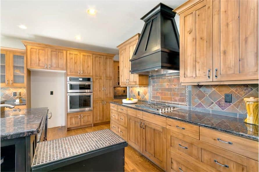 Kitchen with natural wood cabinetry, granite countertops, and a built-in cooktop.