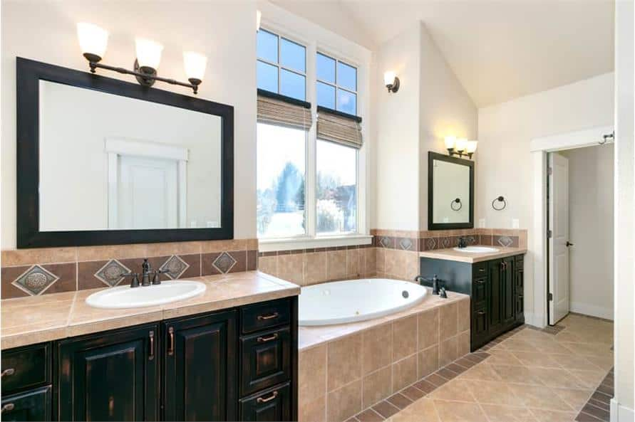 The primary bathroom features his and her sink vanities flanking the drop-in bathtub.