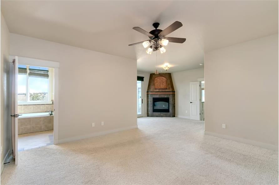 Spacious primary bedroom with carpet flooring, a corner fireplace, and private ensuite.