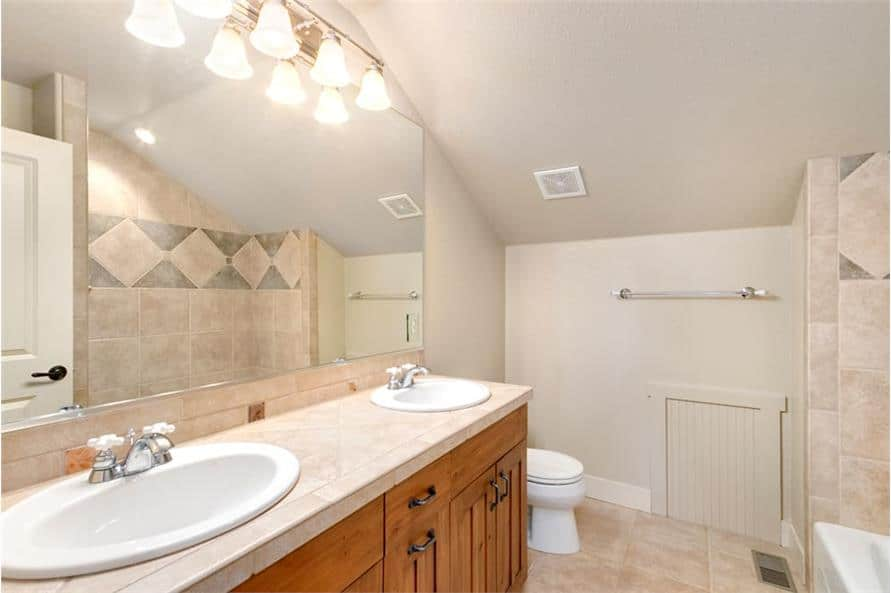 This bathroom is equipped with a toilet and a wooden vanity with double sinks and a large frameless mirror.