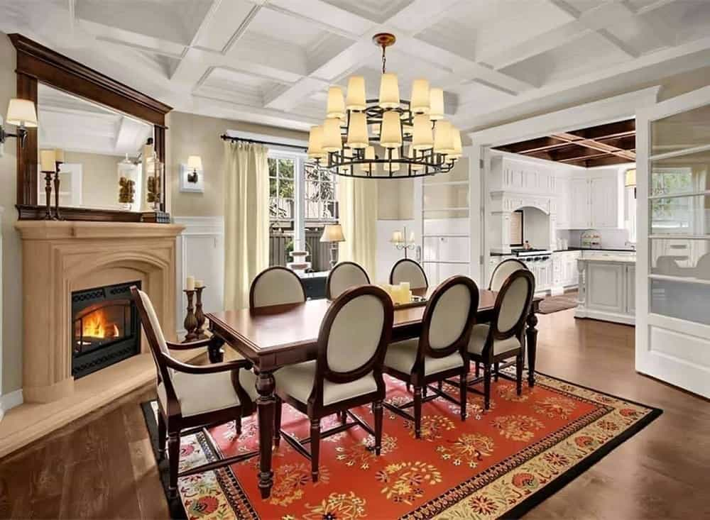 The formal dining room has a large wooden dining table surrounded by cushioned oval back chairs on a patterned area rug by the beige fireplace topped with a mirror.