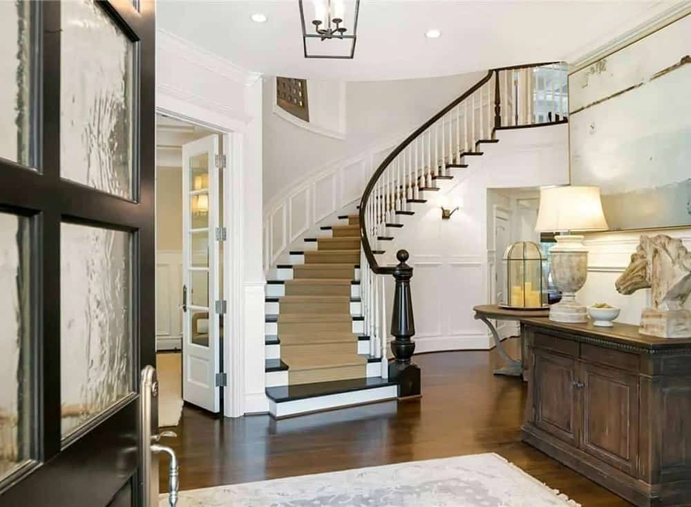 Upon entry of the dark wooden main door, you are welcomed by this foyer that has a dark cabinet topped with decors and a table lamp.