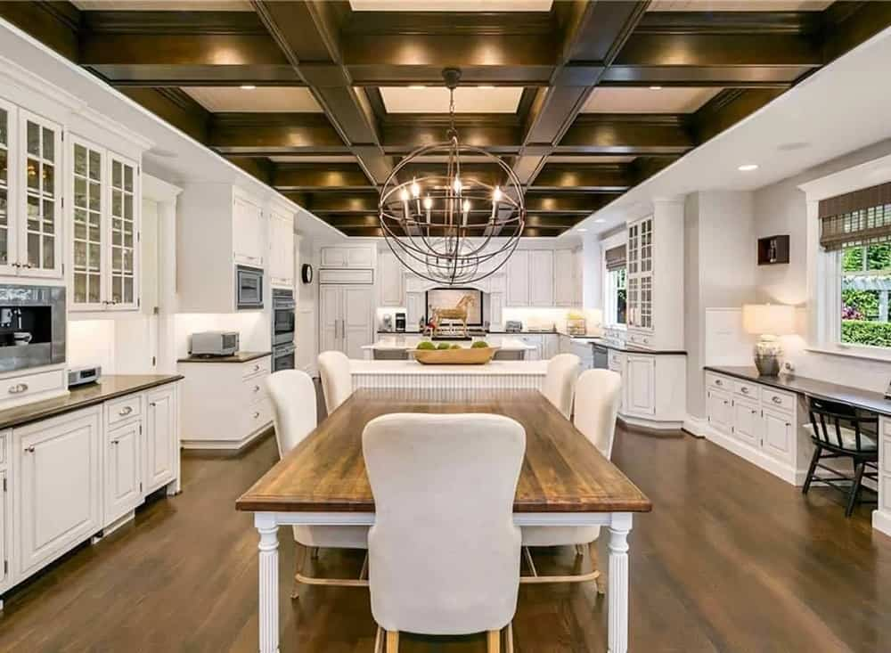 The large kitchen has a rectangular dining table attached to its large beige kitchen island topped with a spherical lighting that hangs from the wooden coffered ceiling.