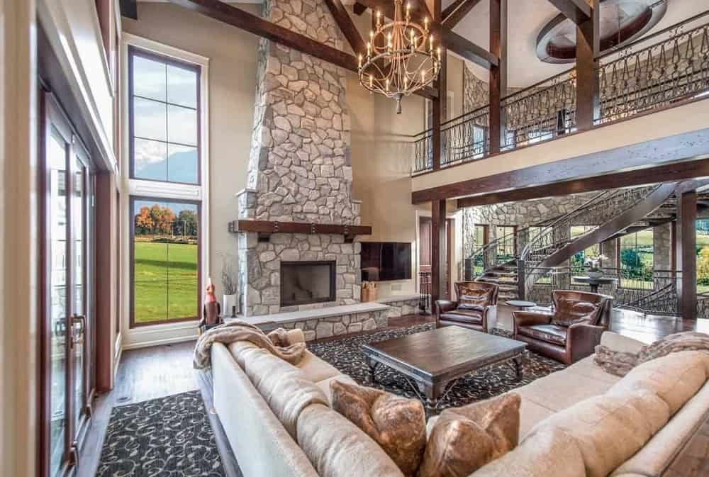 The spacious and airy living room has a large mosaic stone fireplace, an indoor balcony above, a large square wooden coffee table on the patterned area rug and a large beige L-shaped sectional sofa.