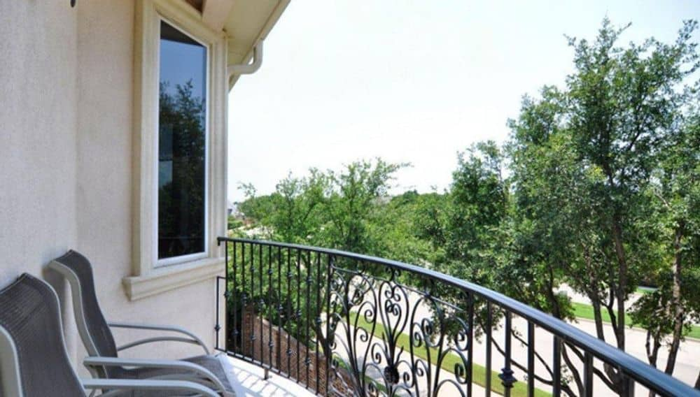Balcony with gray loungers and a wrought iron railing.