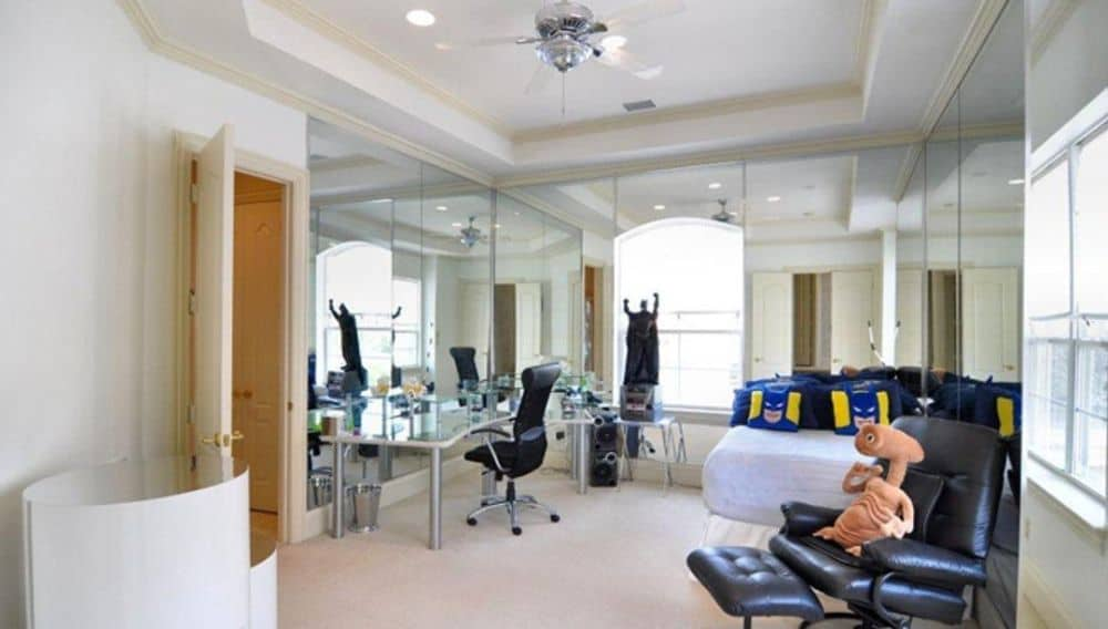This bedroom features mirrored walls, carpet flooring, and a tray ceiling.