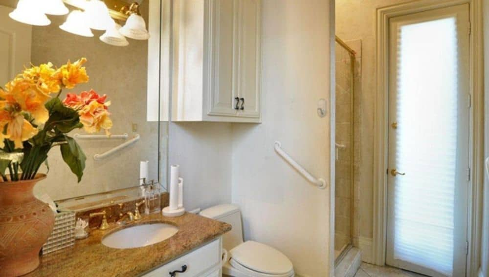 This bathroom is equipped with a sink vanity, a toilet, and a walk-in shower.