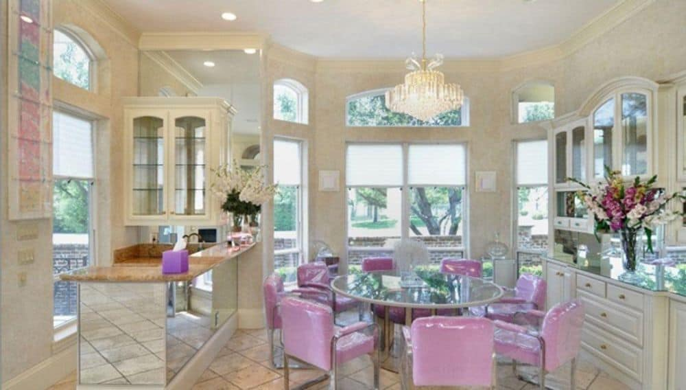 Breakfast nook with a bay window, a built-in bar, and a round dining set topped with a crystal chandelier.