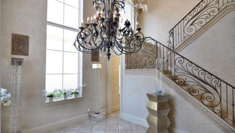 Formal dining room with an ornate chandelier, a tall window, and an elaborate staircase.