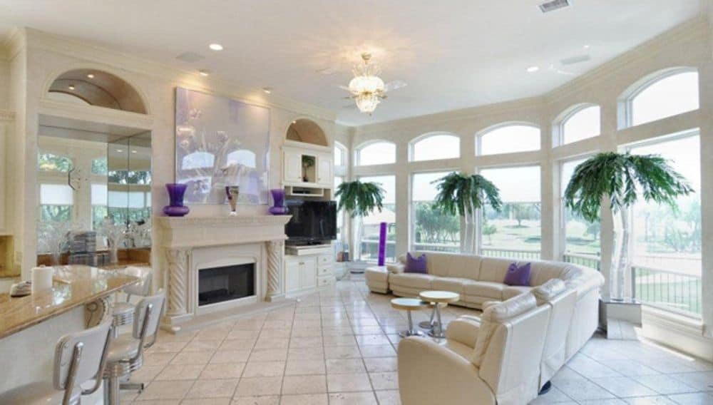 The family room features an arched bow window, a fireplace, and an L-shaped sectional. Purple decors and pillows add a pop of color to the room.