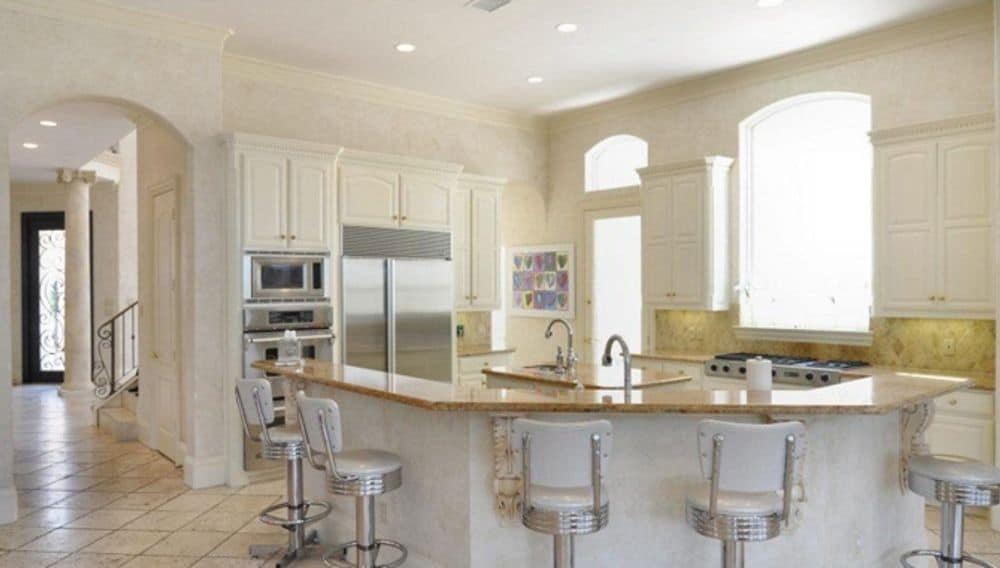 The kitchen offers white cabinetry, a center island, and a curved eating bar paired with round stools.