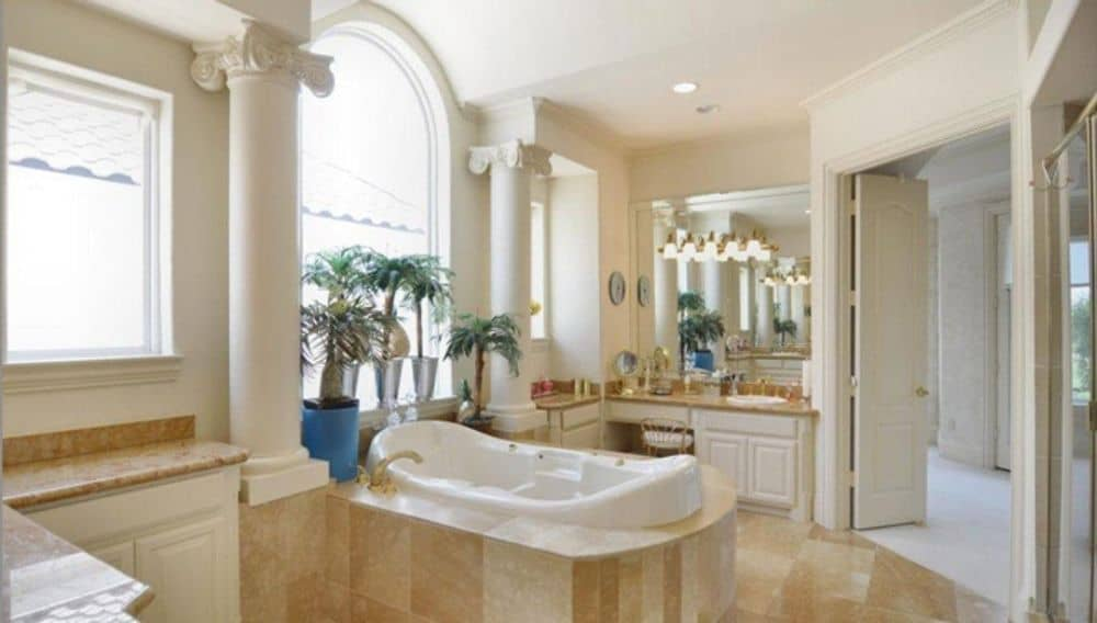Primary bathroom with his and her vanities, a walk-in shower, and a deep soaking tub flanked by interior columns.