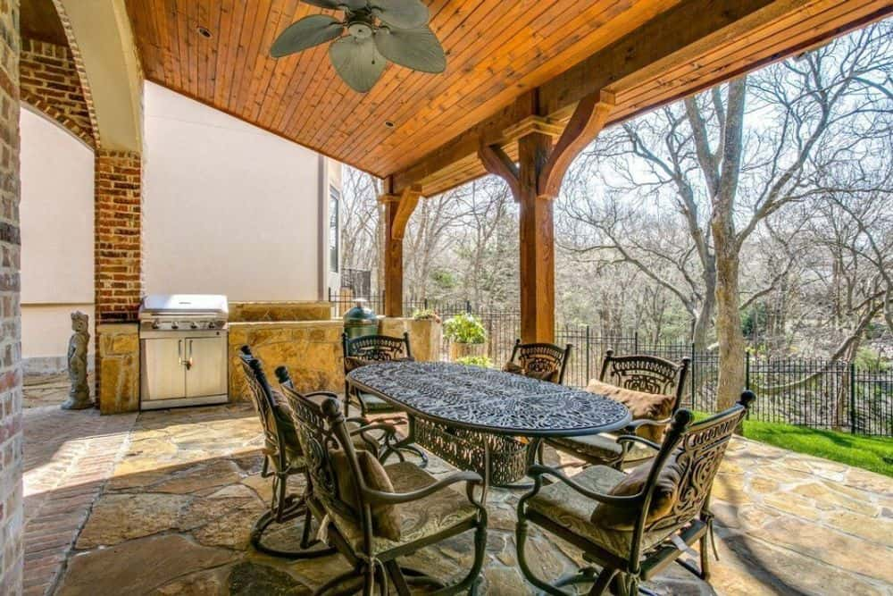 The covered porch is filled with a metal dining set and a summer kitchen with a raised eating bar.