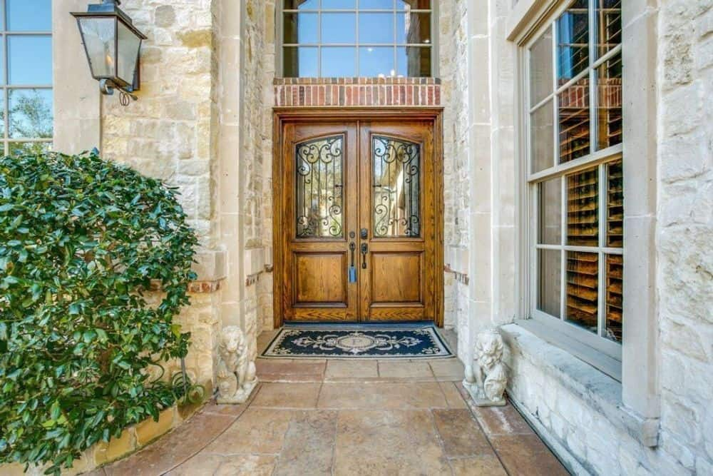 Home entry with a wooden double door complemented with a blue printed rug.