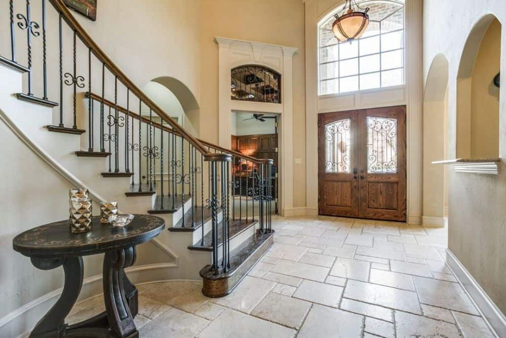 The foyer features a two-story ceiling, an elaborate curved staircase, and a round center table.