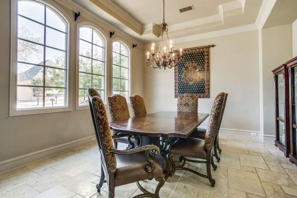 The formal dining room features a classic dining set, a tray ceiling, and arched windows that invite natural light in.