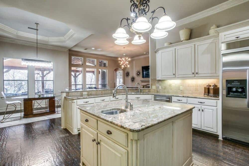 Kitchen with white cabinetry, granite countertops, a center island, and an adjoining breakfast nook.