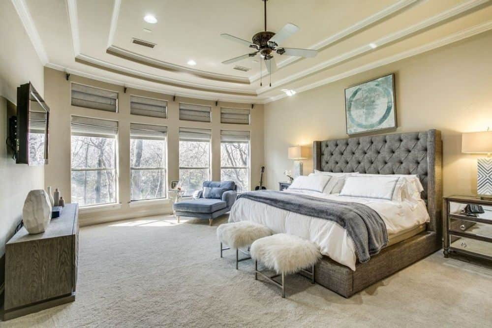 Primary bedroom with a bow window, a stunning step ceiling, and a tufted bed paired with furry footstools.