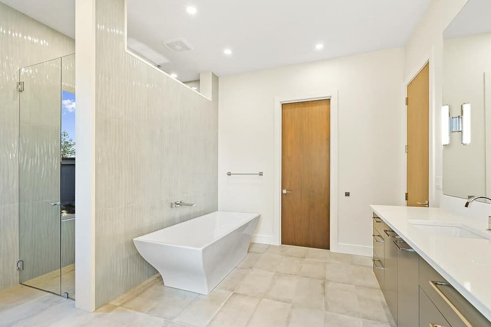 This bathroom has wooden doors, beige walls and beige flooring tiles that make the white freestanding bathtub stand out complemented by the frosted glass wall of the shower area beside it.