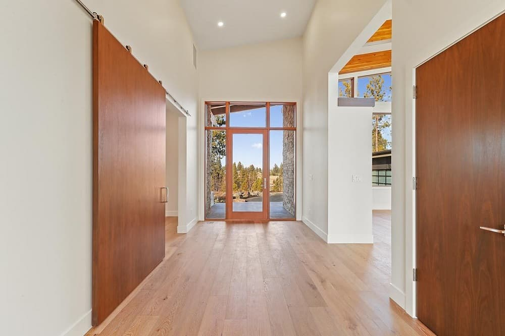 Upon entry into the home, you are welcomed by this simple foyer with a glass door surrounded by glass panels that brighten the beige walls and tall beige ceiling.