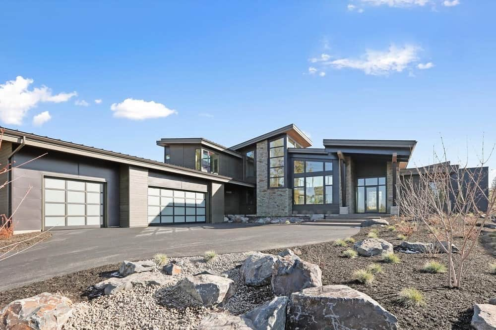 This is a view of the front of the house that has an abundance of glass walls and windows complemented by the concrete driveway, small dessert shrubs and large decorative rocks.