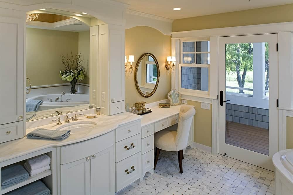 This is a close look at the primary bathroom that has elegant white shaker cabinets and drawers on its vanity across from the corner bathtub adorned with a flower vase.