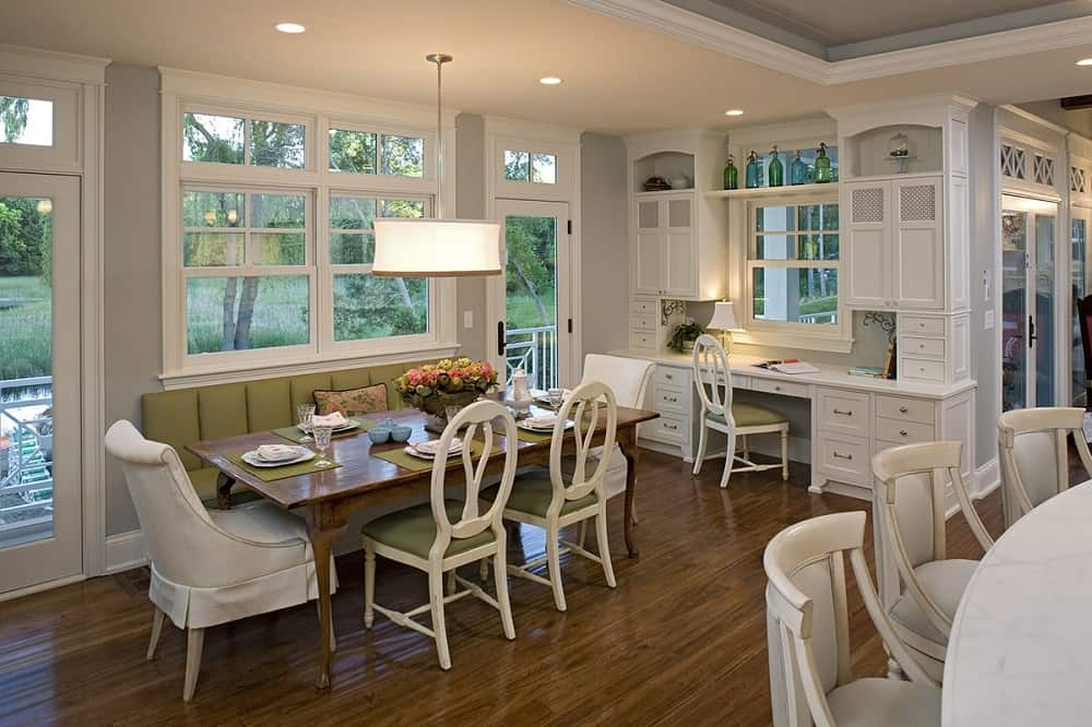 This is the dining area beside the kitchen with a large rectangular wooden dining table paired with a built-in cushioned bench and chairs topped with a pendant drum lighting hanging from a beige ceiling.