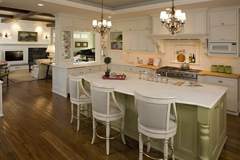 This is a close look at the kitchen that has an avocado green wooden kitchen island across from the cooking area housed in beige shaker cabinets and drawers. These are then complemented by the two chandeliers hanging over the island.