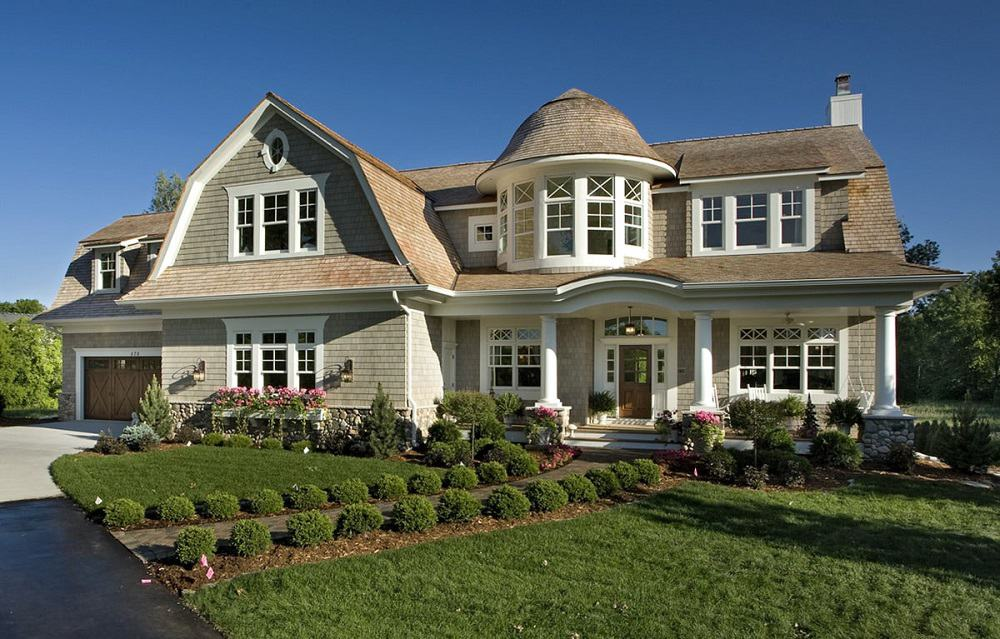 This is a close look at the front of the house with a gambrel roof, a round turret main hall and warm lighting that glows from interior to exterior complemented by the landscaping that has a mosaic stone walkway flanked by grass lawns and shrubs.