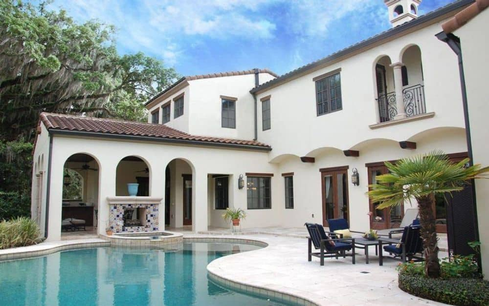 Rear exterior view with outdoor seating, a freeform swimming pool, and a covered lanai bordered by open arches.