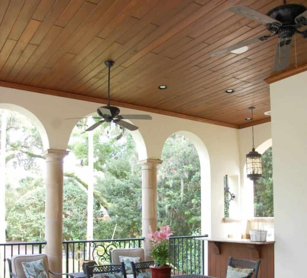 Covered veranda with open arches, wood-paneled ceiling, and a bar.