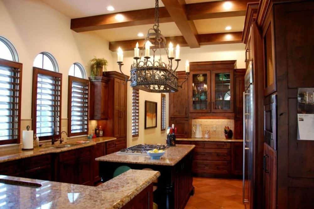 The kitchen offers natural wood cabinetry, granite countertops, a center island, and a wrought iron chandelier hanging from the beamed ceiling.