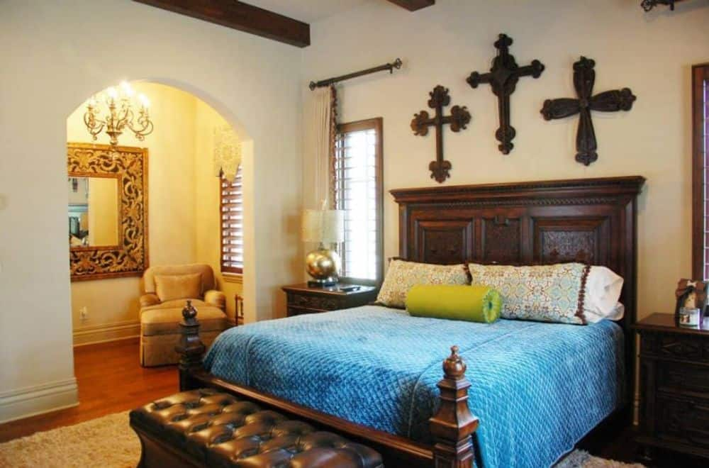 The primary bedroom features a dark wood bed, matching nightstands, a tufted bench, and a sitting area framed with an archway.