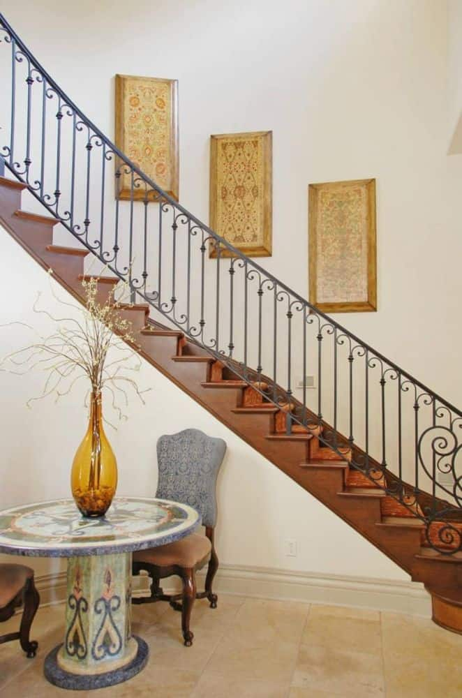 The foyer has a round table, cushioned chairs, and an ornate curved staircase.