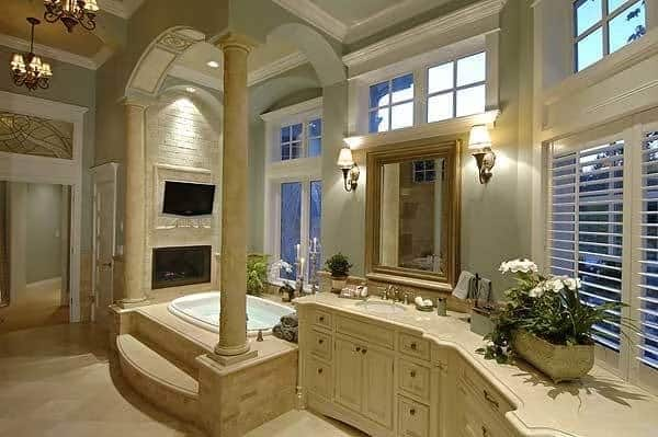 This is the primary bathroom with a large bathtub in its own alcove with a wall-mounted TV and fireplace next to the large vanity that has beige cabinets and drawers.