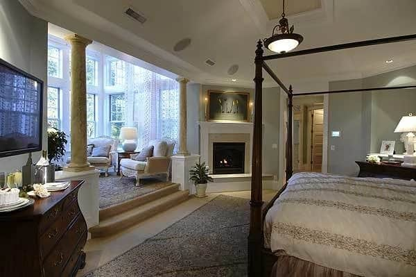 This is the large primary bedroom with a wooden four-poster bed, a fireplace and a large sitting area with cushioned armchairs and tall windows.