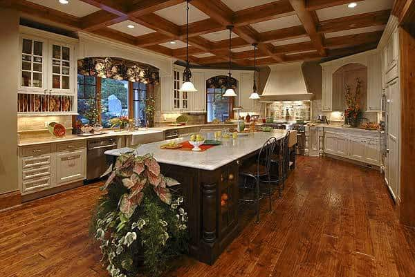 This is a full view of the kitchen that has a large dark wooden kitchen island contrasted by the surrounding shaker cabinets, hardwood flooring and coffered ceiling that hangs pendant lights over the island.
