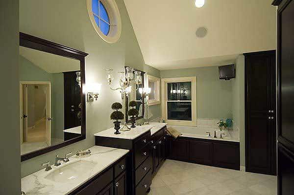 This primary bathroom is dominated by the dark wooden cabinetry of its two-sink vanity contrasted by the white counter. These match well with the bathtub and its housing on the far side under the window.