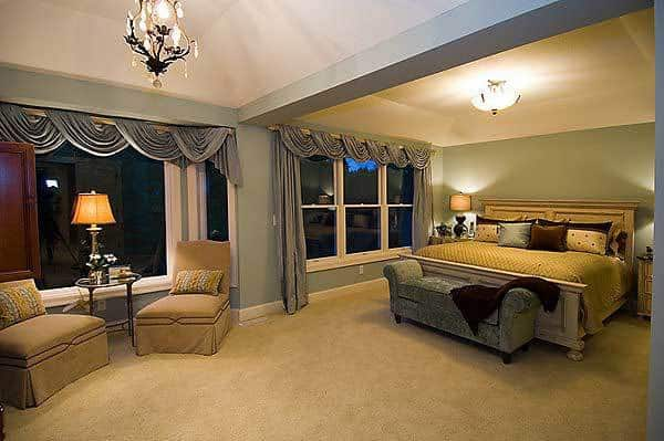 This is the spacious bedroom that has gray and beige walls augmented by the warm lighting coming from the white ceiling and the table lamps flanking the beige traditional bed with a cushioned bench at the foot.