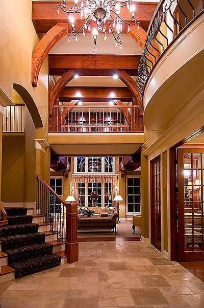 This is the grand foyer with a tall ceiling complemented by the indoor balcony and large wrought-iron chandelier that matches the railings of the stairs.