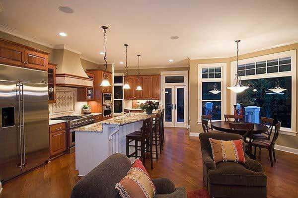 This is a full view of the eat-in kitchen with a round dark wooden dining set on one side of the large two-white kitchen island that has a breakfast bar across from the stainless steel appliances and dark wooden cabinetry.