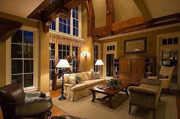 This is the cozy formal living room that has large exposed beams on its tall walls and high ceiling complemented by the large glass window. These pair well with the sofas, wooden coffee table and cabinet.
