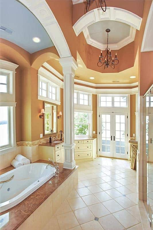 This is a view of the primary bathroom with a large bathtub in the middle housed in a structure with pillars and beige tiles that extend to the flooring and the cabinetry of the vanity.