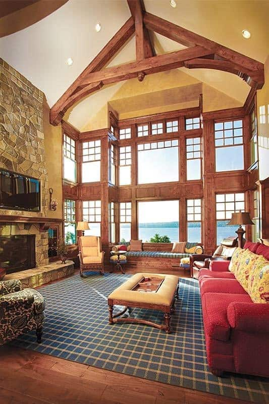 This is the full view of the living room with a high cathedral ceiling adorned with exposed wooden beams. This living room also has a stone mosaic fireplace across from the sofas and cushioned coffee table on the patterned area rug.